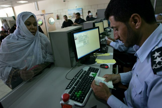 A Palestinian policemen checks the passport of a Palestinian passenger at the Rafah border crossing in the southern Gaza Strip May 28, 2011. After four years, Egypt on Saturday permanently opened the Gaza Strip's main gateway to the outside world, bringing long-awaited relief to the territory's Palestinian. UPI/Ismael Mohamad.
