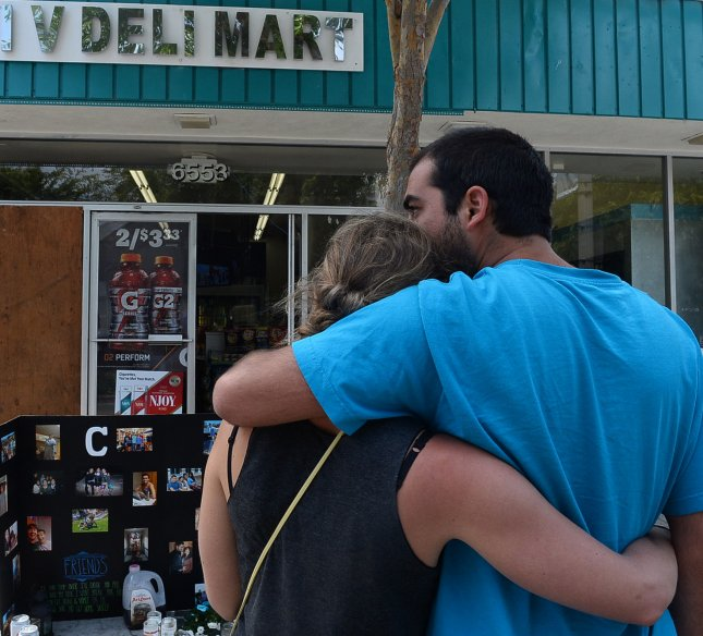 A couple embrace as they stand before a makeshift memorial outside the I.V. Deli Mart in Isla Vista, California on May 26, 2014 where Christopher Michaels-Martinez was gunned down Friday night, one of the scenes of Elliot O. Rodger's rampage. UPI/Jim Ruymen