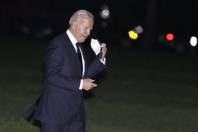 President Joe Biden removes a protective face mask as he walks on the Ellipse as he returns to the White House from Tulsa, Okla., on Tuesday. Photo by Yuri Gripas/UPI