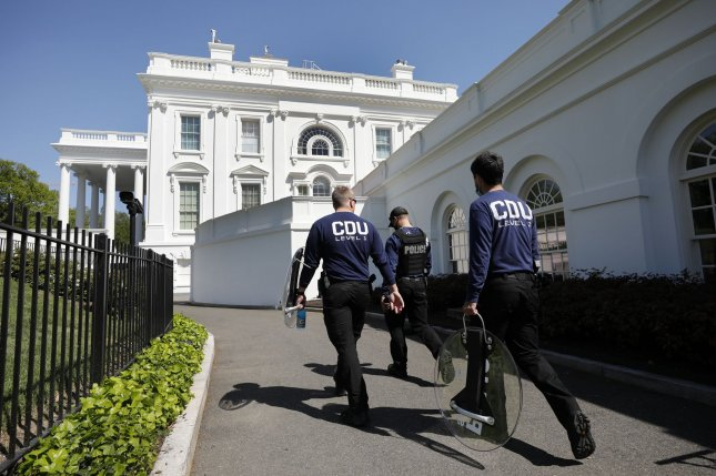 Members of U.S. Secret Service carry riot shields on a driveway at the White House in April. Recent information shows that 881 Secret Service agents contracted COVID-19 during the pandemic. File Photo by Yuri Gripas/UPI