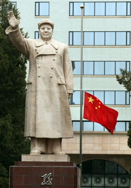 China's national flag flies at half-mast in next to a giant statue of former helmsman Mao Zedong in front of a university in Beijing on April 21, 2010. China held a three-minute period of silence Wednesday, announcing a day of mourning for the Yushu quake victims where over 2,000 people died. UPI/Stephen Shaver