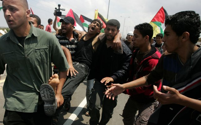 Palestinian carry a wounded man after Israeli troops opened fire during on a massive march heading towards the Erez border crossing in Beit Hanoun northern Gaza , on May 15, 2011, Palestinian medics say one person was killed and 70 others were wounded in the demonstration in the Gaza Strip, commemorating the mass displacement of Palestinians during the war surrounding Israel's establishment in 1948. as a result of which more than 760,000 Palestinians , estimated today to number 4.7 million with their descendants , were pushed into exile or driven out of their homes. UPI/Ismael Mohamad.