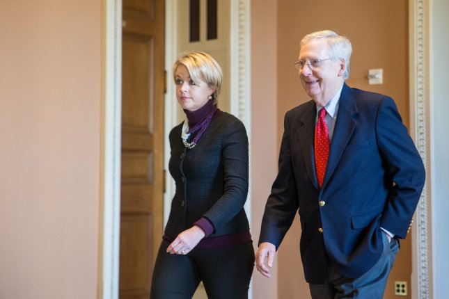 Senate Republican leader Sen. Mitch McConnell, R-Ky., walks with Stephanie Munchow, his director of operations, toward the Senate chamber for a vote on a sweeping tax bill in Washington, D.C, on Friday. Photo by Erin Schaff/UPI