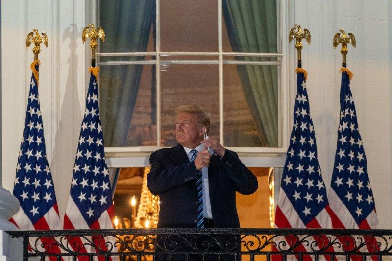 Президент Дональд Трамп снимает свою маску на балконе Трумэна в Белом доме после того, как его выписали из Национального военно-медицинского центра Уолтера Рида после трех дней лечения КОВИД-19. Фото: Ken Cedeno/UPI