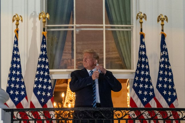 President Donald Trump removes his mask on the Truman Balcony at the White House after being discharged from Walter Reed National Military Medical Center following three days of treatment for COVID-19. Photo by Ken Cedeno/UPI