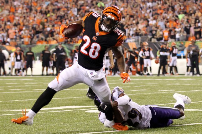 Cincinnati Bengals running back Joe Mixon (28) is tackled by Baltimore Ravens cornerback Marlon Humphrey (29) during the first half of play on Thursday at Paul Brown Stadium in Cincinnati. Photo by John Sommers II/UPI
