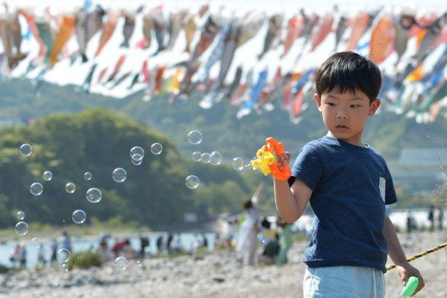 A boy blows soap bubbles at the Sagami River, Kanagawa Prefecture, Japan on May 5. Japanese politicians have been vocal about Japan's low birth rate in the past, and Yoshihide Suga has been criticized for making remarks about women. File Photo by Keizo Mori/UPI