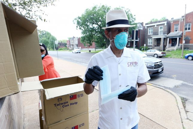 The Rev. Daryl Gray of the Clergy Coalition hands out two face masks at the Lively Stone Church of God in St. Louis on May 26. Pew Research said Friday that African Americans are following news about the coronavirus more closely than any other racial or ethnic group. Photo by Bill Greenblatt/UPI