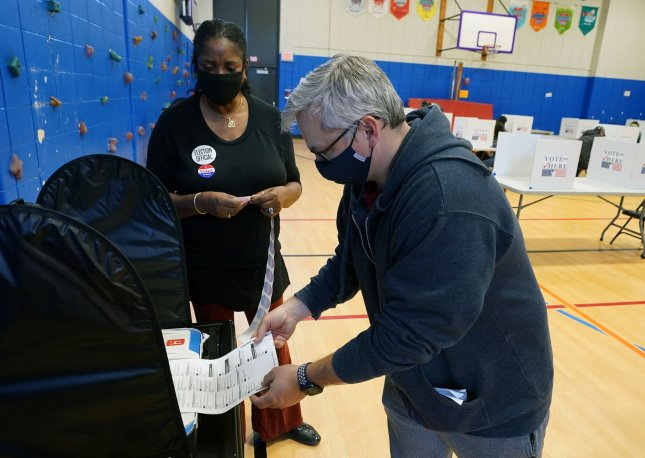 A voter places his vote into a machine at the Craig School in Creve Coeur, Missouri. File Photo by Bill Greenblatt/UPI