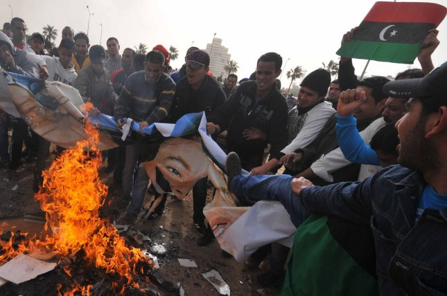 Libyans burn books authored by Libyan leader Moammar Gadhafi and a poster of him at a local park of the Benghazi, Libya on March 2, 2011. Gadhafi warned the West against intervening in the rebellion against his rule. UPI/Mohamaad Hosam