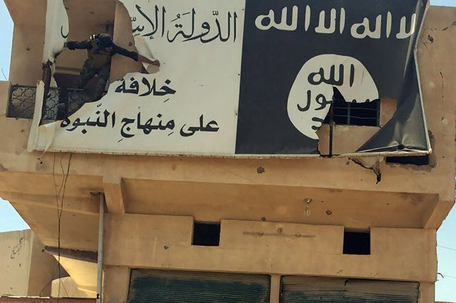 The Islamic State, the flag of which is seen being torn by an Iraqi soldier near Fallujah, is committing genocide against the Yazidi community, a United Nations commission report determined Thursday. File Photo by Abbas Mohammed/UPI