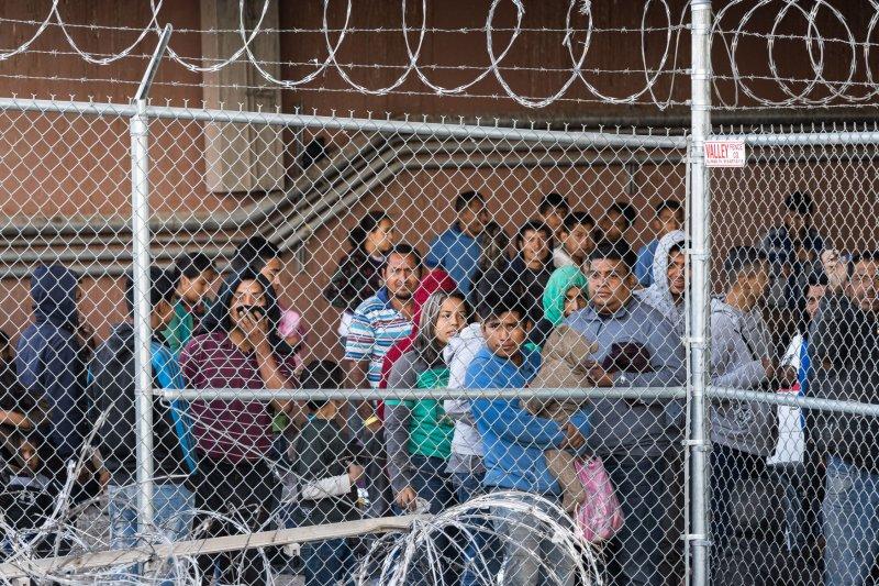Migrants wait for processing under the Paso del Norte Bridge in El Paso, Texas on March 27. File Photo by Justin Hamel/UPI
