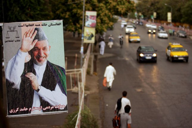 People move through a street as a big banner of Afghanistan President and candidate in the recent presidential election Hamed Karzai hangs from a overpass at left in Kabul, Afghanistan on September 17, 2009. Karzai won 54 per cent of the vote but European observers say that a third of his votes might be suspect due to fraud. UPI/Mohammad Kheirkhah