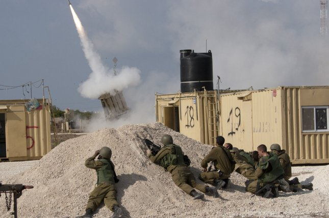 Israeli soldiers take cover as they fire an Iron Dome intercept rocket in southern Israel as Hamas fires rockets into Israel from the Gaza Strip on November 19, 2012. (UPI/Mati Milstein)