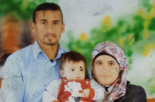 A photo of the Dawabsheh family, holding their 18-month-old son, Ali, who died in an arson attack on their home in by suspected Israeli extremists in Duma, West Bank. The parents and a 4-year-old son were also critically wounded in the attack. Hebrew graffiti was written on the exterior of the house reading price tag and long live Messiah the King. Photo by Zachria Sadeh/Rabbis for Human Rights/UPI
