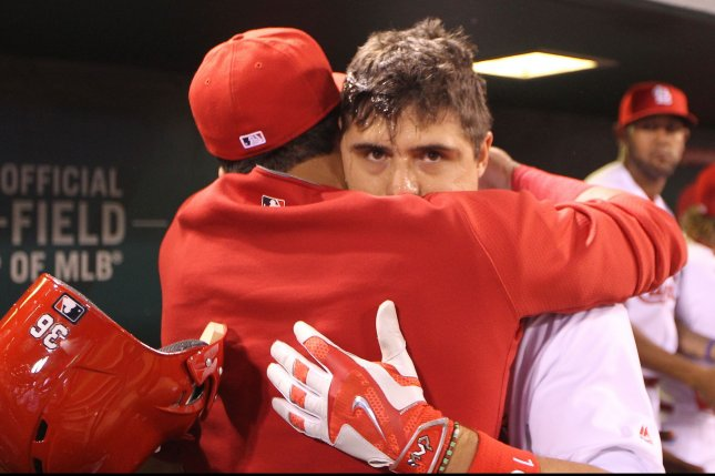 St. Louis Cardinals' Aledmys Diaz is hugged by Carlos Martinez after hitting a grand slam home run in the fourth inning against the Cincinnati Reds at Busch Stadium in St. Louis on September 27, 2016. Photo by Bill Greenblatt/UPI
