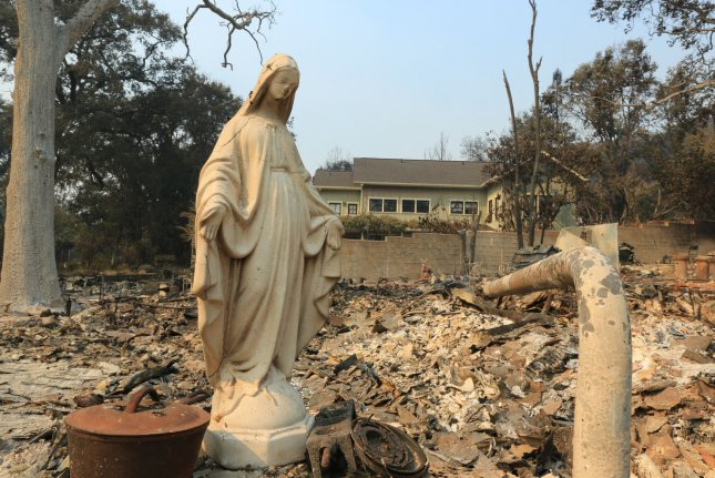 A religious statue stands amid the rubble of a damaged house in Santa Rosa, Calif., on Thursday. Wildfires continue to move through the state's wine country, leaving more than two dozen people dead. Photo by Khaled Sayed/UPI