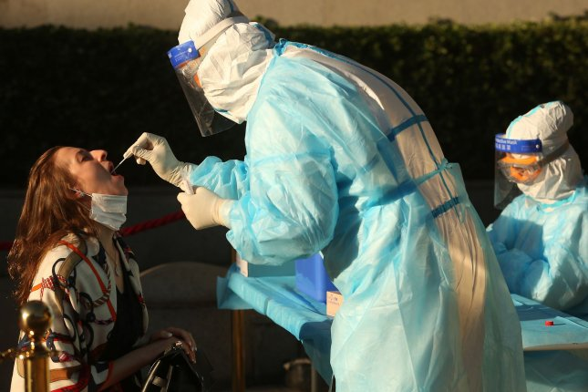 A woman is given a nucleic acid test to detect COVID-19 in Beijing, China, on May 27. Studies said Monday such measures helped to save more than 3 million lives in 11 European nations. Photo by Stephen Shaver/UPI