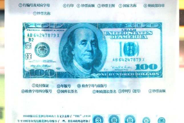 A public service poster posted on the exterior of a Chinese bank explains what U.S. dollar bills look like in hopes of fighting counterfeiting due to the currency's popularity in Beijing on October 15, 2013. China's state-news agency Xinhua published a public commentary arguing that the U.S. debt crisis should prompt a de-Americanized world -- meaning that the American dollar shouldn't be the cornerstone of the world economy. UPI/Stephen Shaver