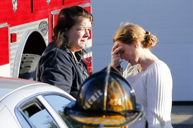 Grief-stricken mourners react as they leave a fire house near Sandy Hook Elementary School in Newtown, Conn. following a shooting that left 26 people dead -- including 20 first-grade children, December 14, 2012. UPI/John Angelillo