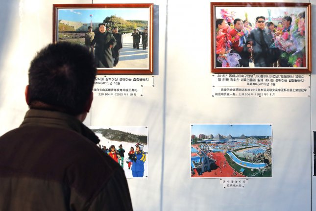 A Chinese man looks at photos of North Korea's leaders posted outside the North Korean embassy in Beijing on January 6. A North Korean defector in the South said she hopes to return to Pyongyang, where she has family. Photo by Stephen Shaver/UPI