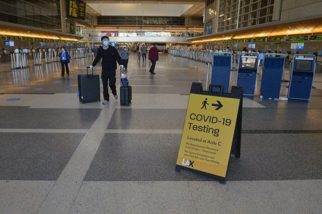 Masked travelers walk through a nearly empty terminal at Los Angeles International Airport in Los Angeles, Calif., on November 25. A sign in the foreground announces availability of coronavirus testing at the airport, which is one of the United States' busiest hubs for international travel. File Photo by Jim Ruymen/UPI