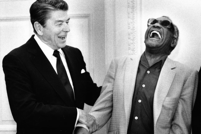 President Ronald Reagan jokes with singer/pianist Ray Charles on June 20, 1985 on a visit to the Oval Office of the White House in Washington. Photo by Vince Mannino/Files