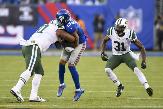 New York Giants wide receiver Odell Beckham (13) gets hit hard by New York Jets defensive end Sheldon Richardson (91). Photo by Rich Kane/UPI