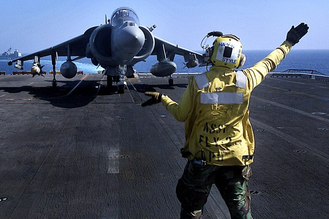 A flight deck handler directs an AV-8B Harrier jet from the 15th Marine Expeditionary Unit to takeoff position for a mission over Afghanistan on November 7, 2001. File Photo by Joseph R. Chenelly/U.S. Navy/UPI