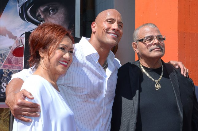 Professional wrestler Rocky Johnson (R) attends the hand and footprint ceremony immortalizing his son, actor Dwayne The Rock Johnson (C) in Hollywood, Los Angeles, in 2015. Photo by Jim Ruymen/UPI