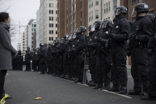 A protester faces riot police in Washington, D.C., on Friday amid the inauguration of President Donald Trump. D.C. police said late Friday that more than 200 people had been arrested for disruptive and violent conduct in the city intended as demonstrations against Trump taking office. Photo by Skye McKee/UPI