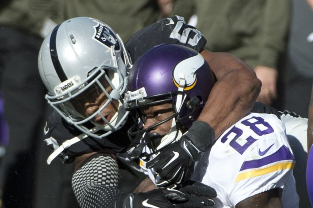 Minnesota Vikings RB Adrian Peterson (28) is brought down by former Oakland Raiders linebacker Malcolm Smith in the first quarter at O.co Coliseum in Oakland, California on November 15, 2015. File photo by Terry Schmitt/UPI
