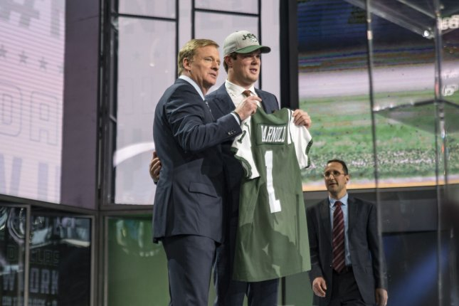 Former USC quarterback Sam Darnold holds his New York Jets jersey with NFL commissioner Roger Goodell after Darnold was selected with the third overall pick in the NFL draft. Photo by Sergio Flores/UPI