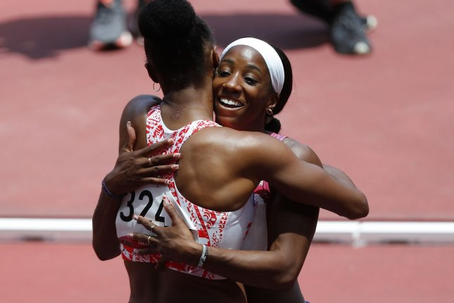 Gold medalist Jasmine Camacho-Quinn (L) of Puerto Rico hugs silver medalist Kendra Harrison of Team USA after the women's 100-meter hurdles at the 2020 Summer Games on Monday in Tokyo. Photo by Bob Strong/UPI