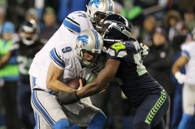 Detroit Lions quarterback Matthew Stafford (9) is sacked by Seattle Seahawks defensive end Cliff Avril (56). File photo by Jim Bryant/UPI