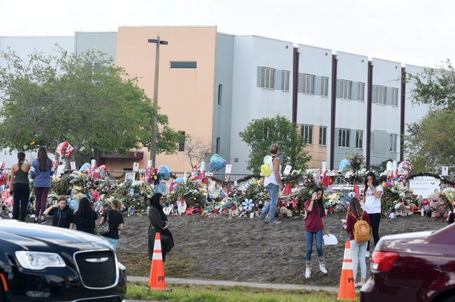 Students walk past the freshman building at Marjory Stoneman Douglas High School in Parkland, Fla., two weeks after a school shooting the building. On Monday, Broward Public School reassigned four staff members from the school. Photo by Gary Rothstein/UPI
