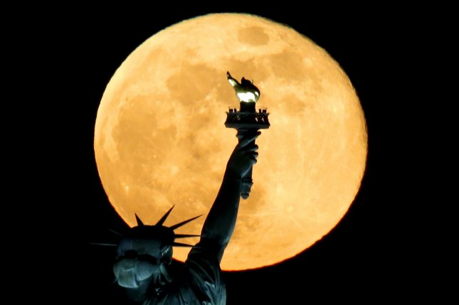 A full moon rises behind the Statue of Liberty in New York City on May 7.September was graced by the Corn Moon, summer's last full moon, on Tuesday and Wednesday. File Photo by John Angelillo/UPI