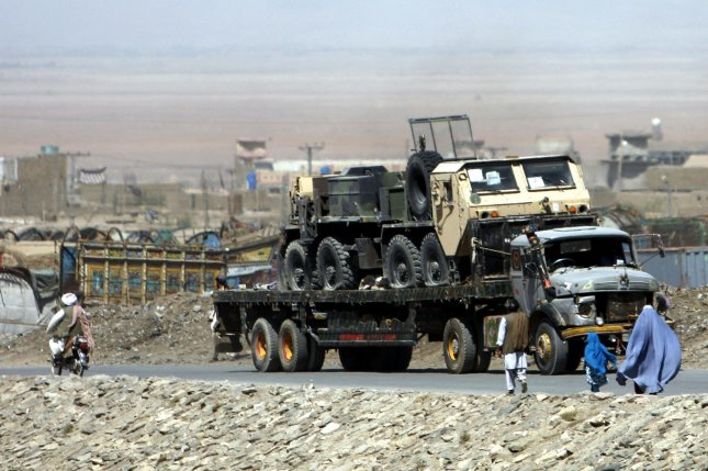 Residents in traditional dress walk past departing NATO and U.S. military vehicles from U.S. base in Kandahar, Afghanistan at Chaman, Pakistan to the port of Karachi on September 3, 2013. The present 70,000 U.S. Troops will be cut to 34,000 by February 2014, but the NATO commander Lt. Gen. Mark Milley said on September 4, 2013, that there has been no discussions that the coalition would completely withdraw by the end of 2014. UPI/Matiullah