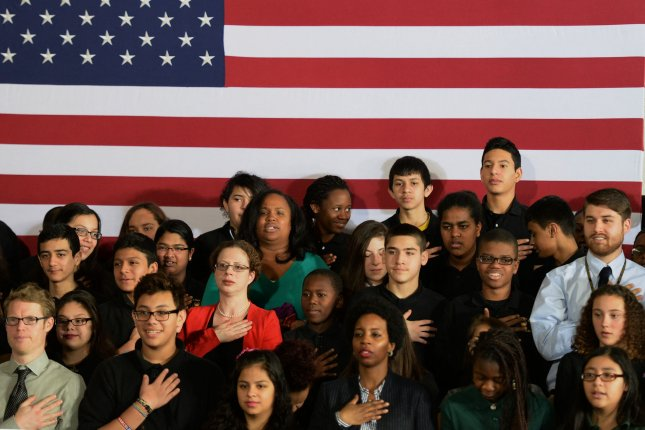 Teachers and students recite the Pledge of Allegiance prior to the arrival of President Barack Obama who unveiled a speedup to his ConnectED initiative at Buck Lodge Middle School in Adelphi, Maryland on February 4, 2014. ConnectED is to provide high-speed Internet to all students in American schools. In addition to the Federal Communications Commission directing $2 billion for that purpose, several companies are donating $750 on digital tablets, computers and software. Photo by Pat Benic/UPI
