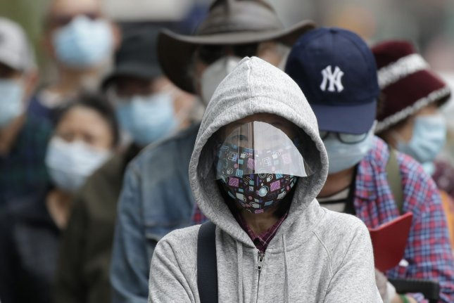 TD Bank customers wear protective face masks as they wait in line for hours to enter a Chinatown bank branch in New York City on Thursday. Photo by John Angelillo/UPI