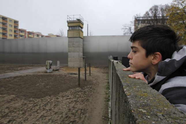 A boy looks over an original segment of the Berlin Wall at the Bernauer Strasse memorial on the 20th anniversary of the fall of the Wall on November 9, 2009 in Berlin. On November 9, 1989, East Germany announced free passage for its citizens through border checkpoints, rendering the Berlin Wall virtually irrelevant. File Photo by David Silpa/UPI