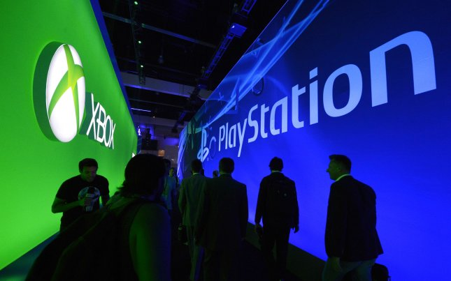 Attendees pass between the XBox and PlayStation displays during E3, the Electronic Entertainment Expo held at the LA Convention Center in Los Angeles on June 11, 2013. UPI/Phil McCarten