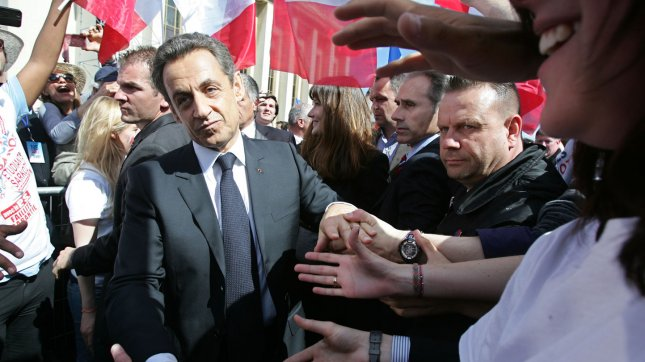 French incumbent President Nicolas Sarkozy shakes hands during a party rally on May Day ahead of the second round of votes for the presidential elections in Paris, France, on May 1, 2012. UPI/Eco Clement