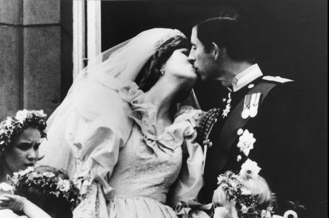 In the year's big happy story, the Prince and Princess of Wales kiss on the balcony of Buckingham Palace after their wedding at St. Paul's Cathedral on July 29, 1981. The heir to the British throne, Prince Charles, married the Lady Diana Spencer to the delight of millions. (UPI Photo/Files)