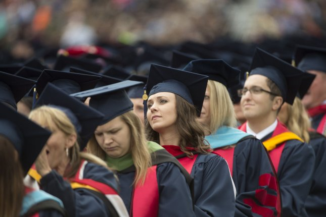 Students listen while President Donald Trump delivers the commencement speech for Liberty University graduates, in Lynchburg, Va., on May 13. Students planning to borrow after July 1 will have to pay higher interest rates. File Photo by Molly Riley/UPI