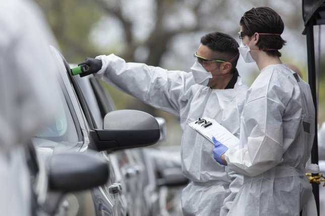 Hayward emergency-medical technicians check members of the public for symptoms and high temperature at a coronavirus drive-up station in Hayward, Calif., on March 23. CVS is opening new drive-through testing sites in some locations. Photo by Peter DaSilva/UPI