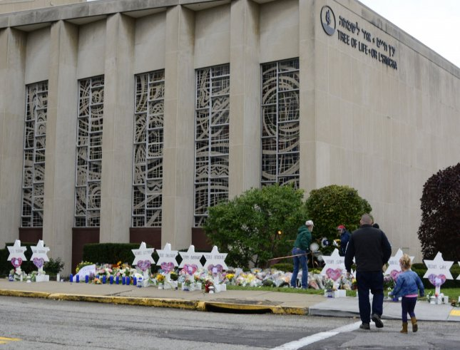 A father leads his daughter to the temporary memorial outside the Tree of Life Synagoguein the Squirrel Hill neighborhood of Pittsburgh in October 2018 where 11 people died during a mass shooting. Photo by Archie Carpenter/UPI