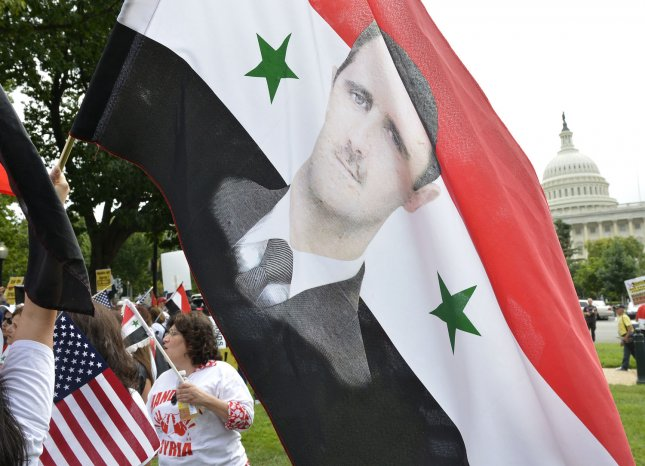Pro-Syrian regime demonstrators hold a flag with the image of Syrian President Bashar Assad during a rally on Capitol Hill, September 9, 2013, in Washington, DC. UPI/Mike Theiler