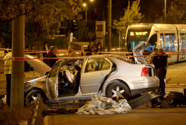 Israeli police stand at the scene of a terror attack where a Palestinian drove his car into a crowd of people waiting for the light rail on Ammunition Hill in Jerusalem, Israel, October 22, 2014. UPI/stringer