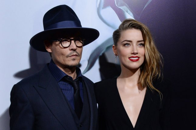 Amber Heard (R) with husband Johnny Depp at the Los Angeles premiere of '3 Days to Kill' on February 12, 2014. The actress faces two charges of illegally importing animals in Australia for bringing the couple's dogs into the country in May. File photo by Jim Ruymen/UPI